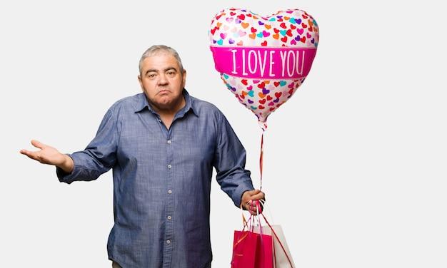 Uomo di mezza età che celebra il giorno di san valentino confuso e dubbioso