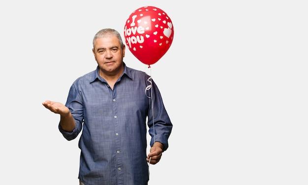 Uomo di mezza età che celebra il giorno di san valentino tenendo qualcosa sulla mano di palma