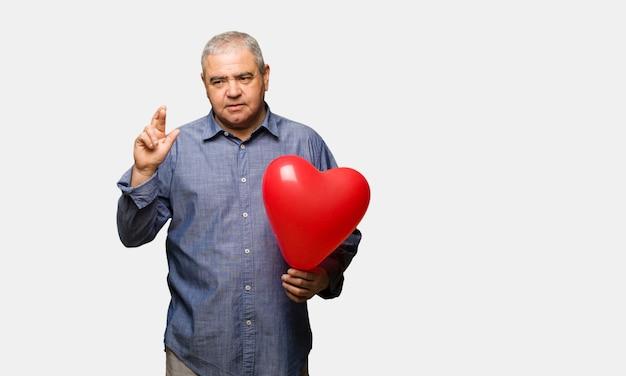 Uomo di mezza età che celebra le dita di incrocio di san valentino per avere fortuna