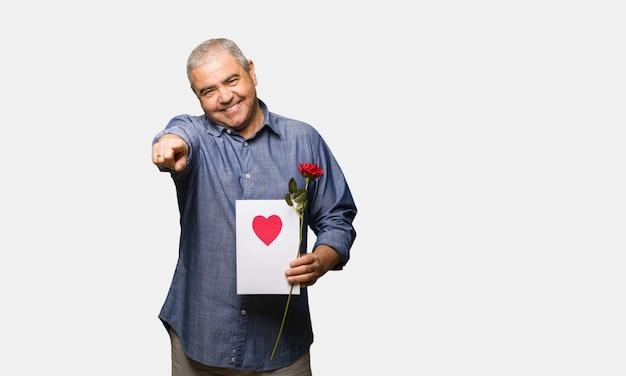 Uomo di mezza età che celebra san valentino allegro e sorridente