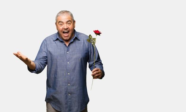 Uomo di mezza età che celebra san valentino celebrando una vittoria o successo