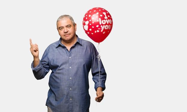 Uomo di mezza età che celebra san valentino che punta verso il lato con il dito