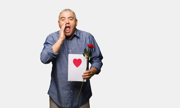 Uomo di mezza età che celebra san valentino gridando qualcosa di felice per la parte anteriore