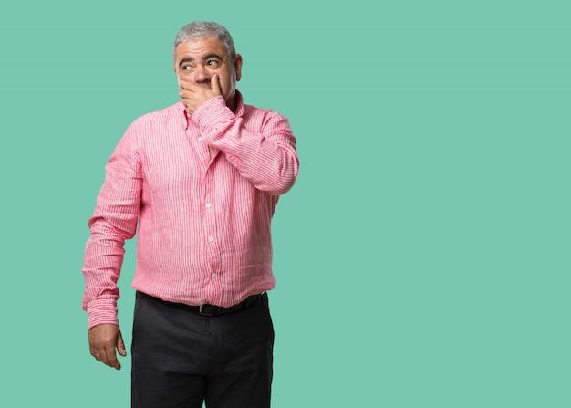Uomo di mezza età che copre la bocca, simbolo del silenzio e della repressione, cercando di non dire nulla