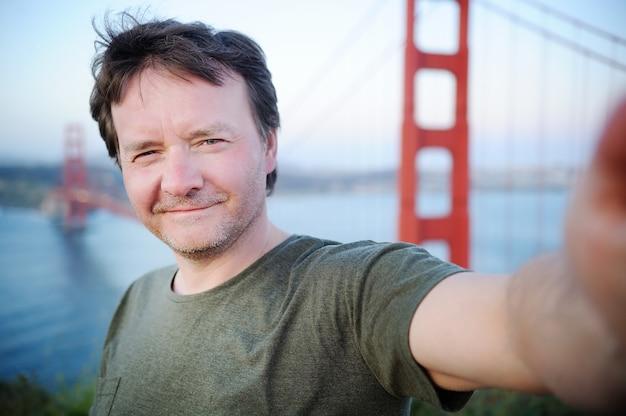 Uomo di mezza età che fa un autoritratto (selfie) con il famoso golden gate bridge a san francisco, california, usa