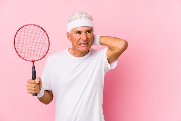 Uomo di mezza età che gioca a badminton isolato toccando la parte posteriore della testa, pensando e facendo una scelta.