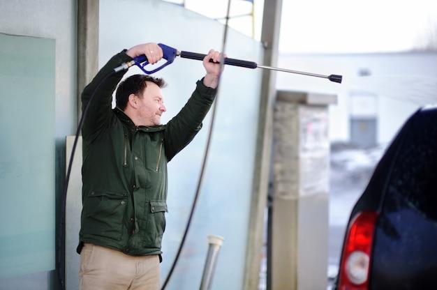 Uomo di mezza età che lava un'automobile su un autolavaggio. auto pulita