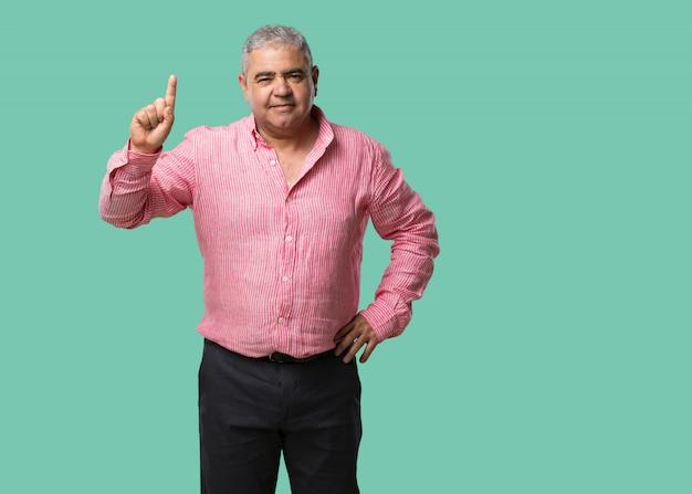 Uomo di mezza età che mostra il numero uno, simbolo del conteggio, concetto di matematica