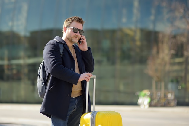 Uomo di mezza età che parla al telefono nella stazione centrale.