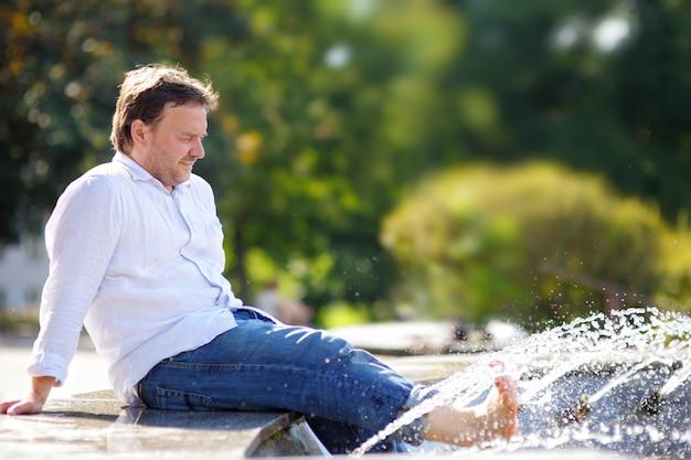 Uomo di mezza età che si diverte in una fontana della città