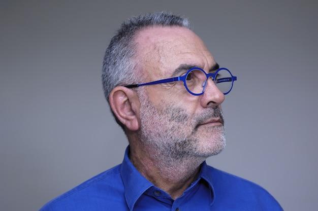 Uomo di mezza età con camicia blu e occhiali