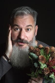 Uomo di mezza età con la barba che tiene un mazzo invernale di ramoscelli di abete nobil, coni, pistacchio, leucodendro ed edera, concetto di regalo invernale