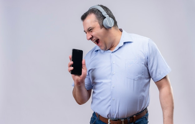 Uomo di mezza età con la faccia che urla ascoltando qualcosa in cuffie che mostra il suo smartphone su uno sfondo bianco