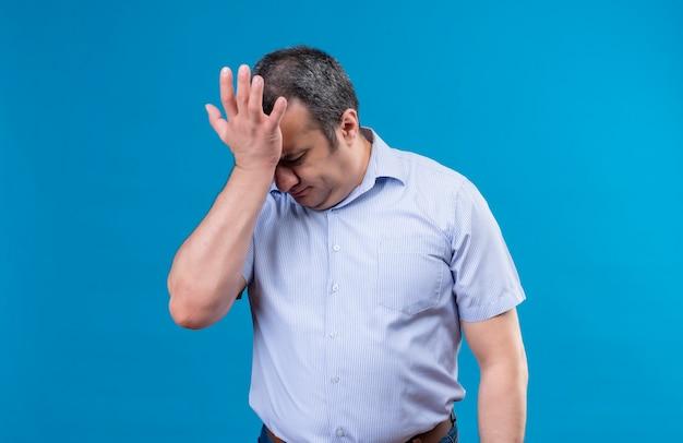 Uomo di mezza età cupo e depresso in camicia a righe verticali blu che tiene la mano sulla fronte su uno spazio blu