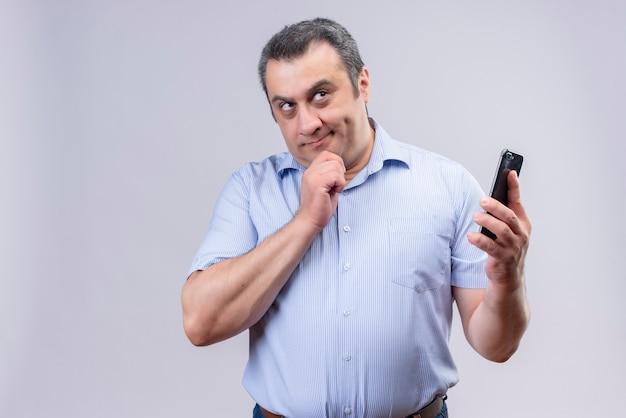 Uomo di mezza età di pensiero che indossa la maglietta spogliata blu che tiene il suo telefono cellulare con la mano mentre levandosi in piedi su una priorità bassa bianca