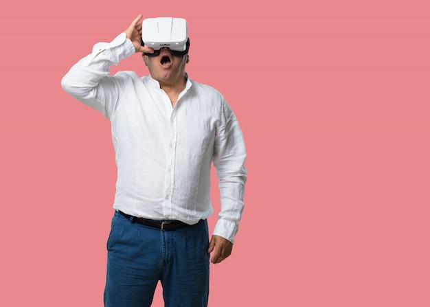 Uomo di mezza età entusiasta e divertito, giocando con gli occhiali della realtà virtuale, esplorando un mondo fantastico, cercando di toccare qualcosa