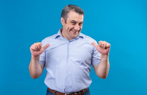 Uomo di mezza età felice ed emozionato in camicia a strisce blu che indica a se stesso e che mi chiama gesto con la mano su uno spazio blu