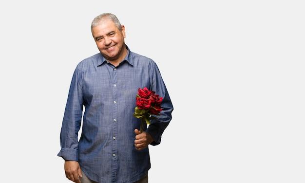 Uomo di mezza età festeggia il giorno di san valentino allegro con un grande sorriso