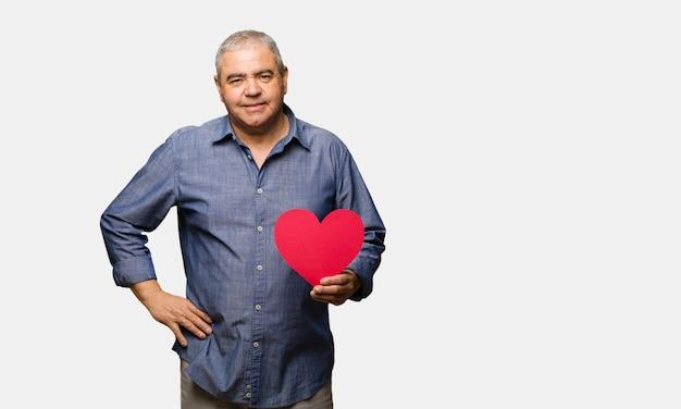 Uomo di mezza età festeggia il giorno di san valentino con le mani sui fianchi