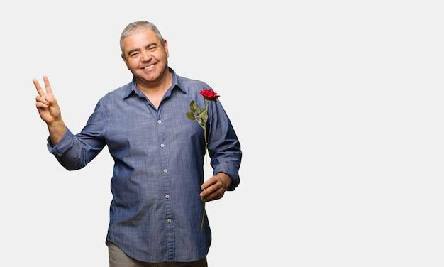 Uomo di mezza età festeggia il giorno di san valentino facendo un gesto di vittoria