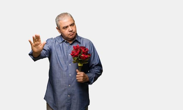 Uomo di mezza età festeggia il giorno di san valentino mettendo la mano davanti