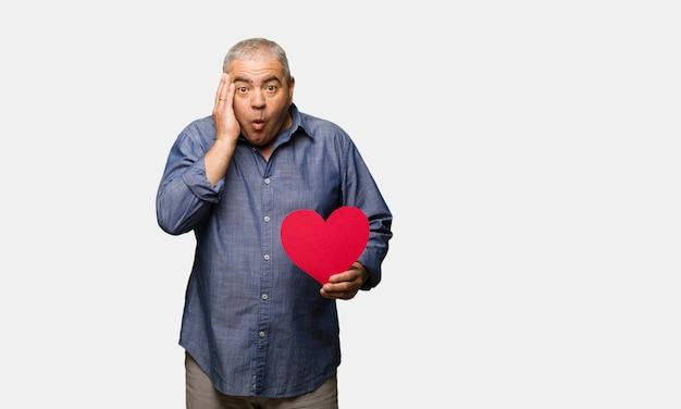 Uomo di mezza età festeggia il giorno di san valentino sorpreso e scioccato