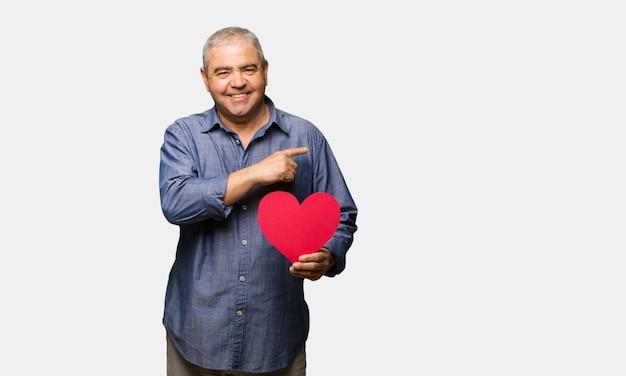 Uomo di mezza età festeggia il giorno di san valentino sorridendo e indicando il lato