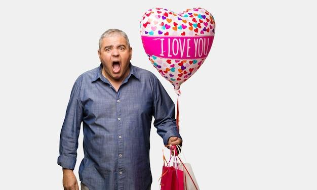 Uomo di mezza età festeggia il giorno di san valentino urlando molto arrabbiato e aggressivo
