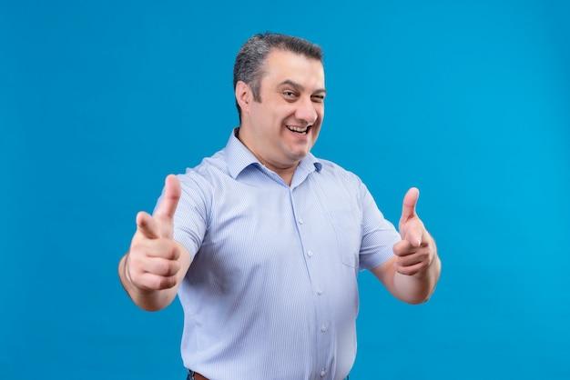 Uomo di mezza età gioioso e sorridente in camicia a strisce blu che indica con il dito indice e ammiccante alla macchina fotografica su una priorità bassa blu