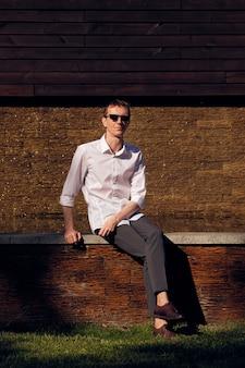 Uomo di mezza età in occhiali da sole seduti in ombra in una calda giornata di sole