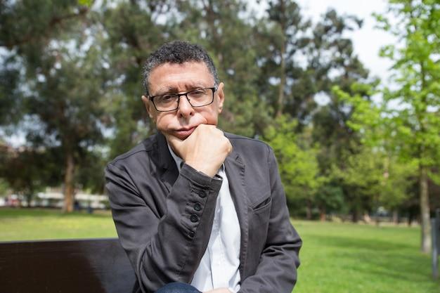 Uomo di mezza età pensieroso che si siede sulla panchina nel parco della città