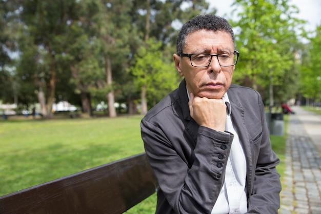 Uomo di mezza età premuroso che si siede sul banco nel parco della città
