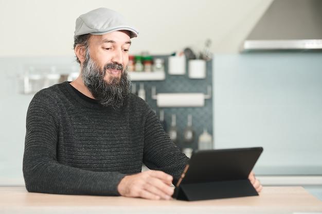 Uomo di mezza età sorridente con una barba e un cappuccio che fanno una videoconferenza a casa