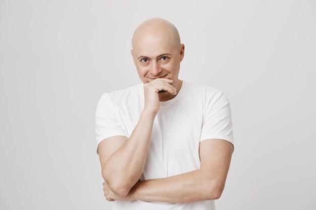 Uomo di mezza età sorridente eccitato in una risatina bianca della maglietta