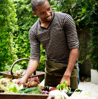 Uomo di origine africana con vari ortaggi biologici freschi