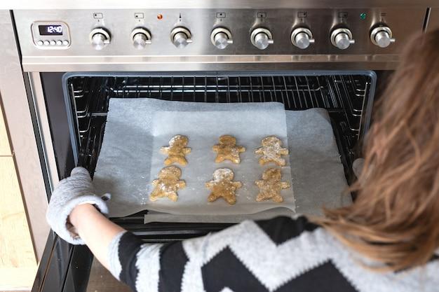 Uomo di pan di zenzero nel forno di cottura, donna che produce i biscotti fatti in casa dell'uomo di pan di zenzero nel forno