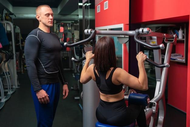 Uomo di personal trainer che lavora con la giovane donna in palestra moderna