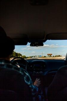 Uomo di prospettiva scarsamente illuminato alla guida di un'auto