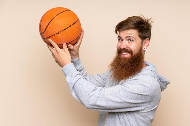 Uomo di redhead con barba lunga con palla di basket