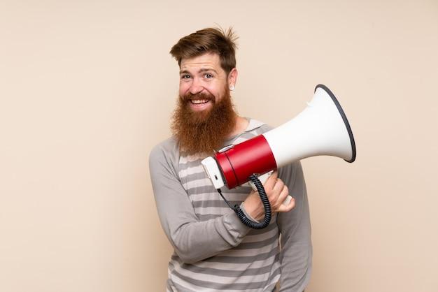 Uomo di redhead con barba lunga in possesso di un megafono