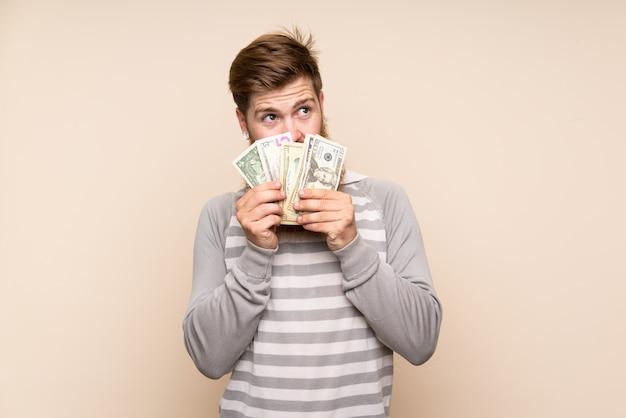 Uomo di redhead con barba lunga prendendo un sacco di soldi