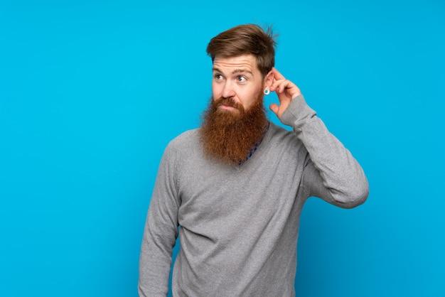 Uomo di redhead con barba lunga sopra isolato blu avendo dubbi