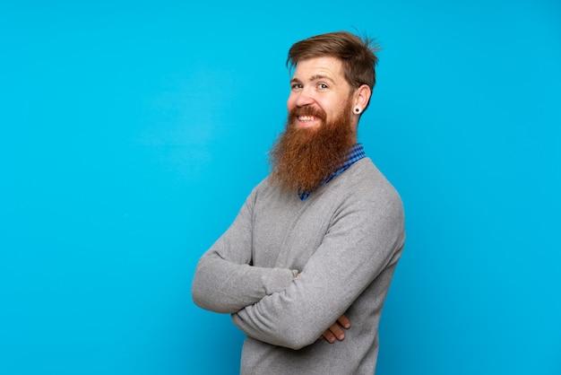 Uomo di redhead con barba lunga sopra isolato blu con le braccia incrociate e guardando avanti
