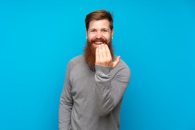 Uomo di redhead con barba lunga sopra isolato blu invitante a venire con la mano. felice che tu sia venuto