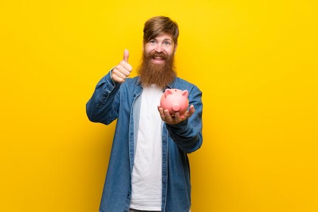 Uomo di redhead con barba lunga sopra isolato muro giallo in possesso di un grande salvadanaio