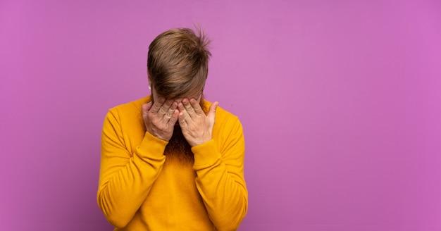 Uomo di redhead con barba lunga sopra viola isolato con espressione stanca e malata