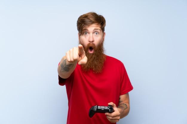 Uomo di redhead con la barba lunga che gioca con un controller di videogioco sorpreso e che punta davanti