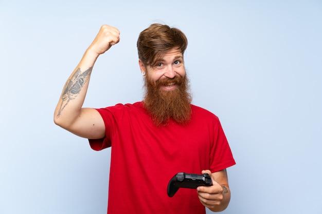 Uomo di redhead con la barba lunga, giocando con un controller di videogioco che celebra una vittoria