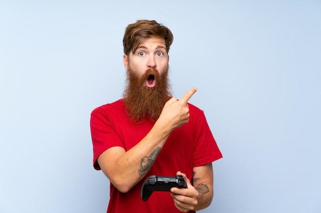 Uomo di redhead con la barba lunga, giocando con un controller di videogioco sorpreso e indicando il lato