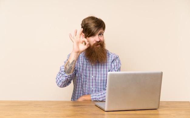Uomo di redhead con la barba lunga in una tabella con un computer portatile che mostra un segno giusto con le dita